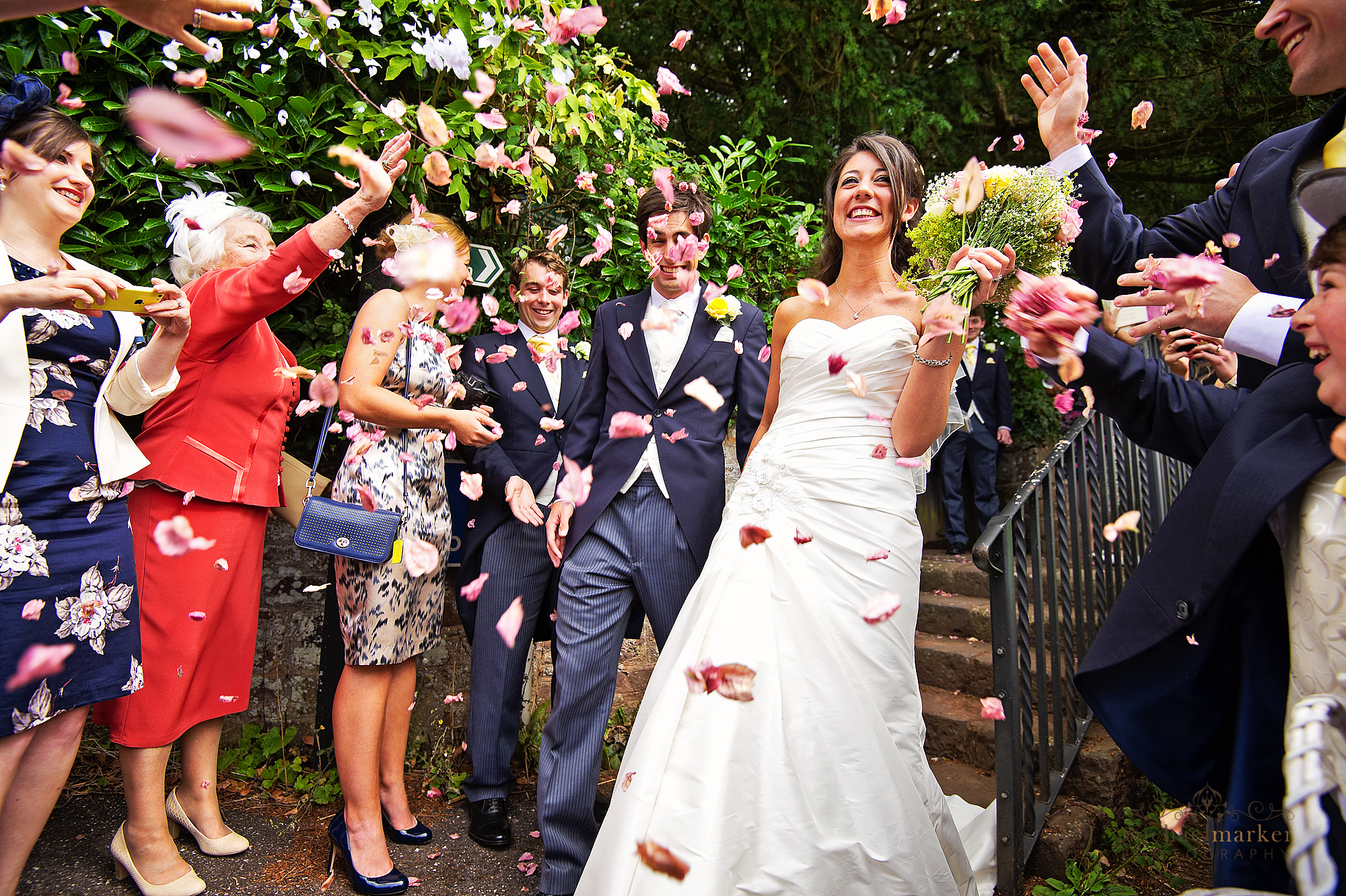 Bride and groom walking through confetti at Bickleigh Church in Devon