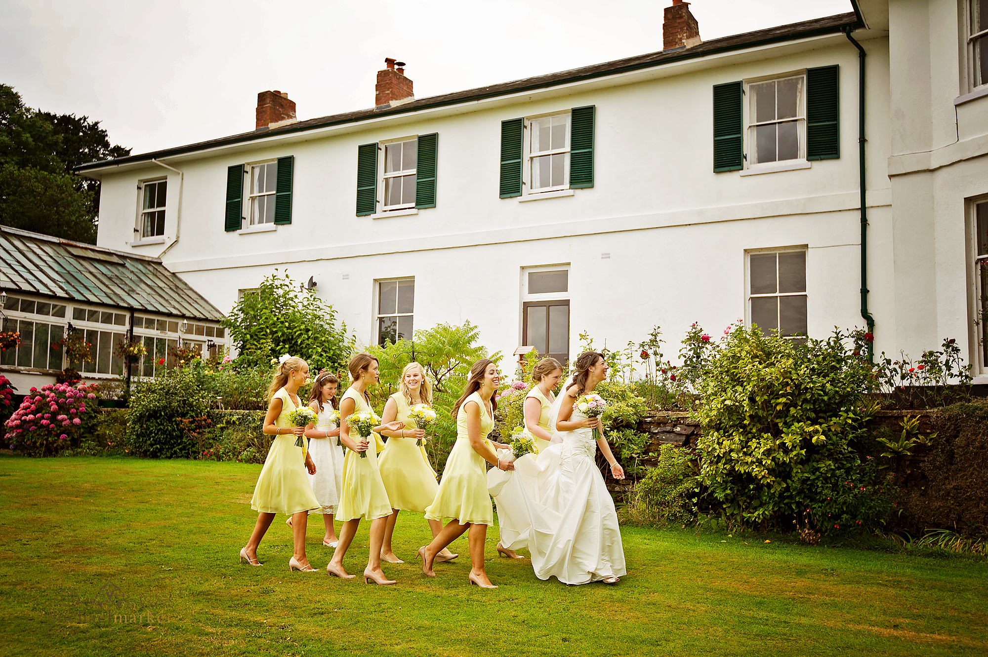 Bride and bridesmaids walking on grass outside family home in Devon