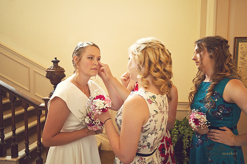 Bride wiping a tear before wedding ceremony