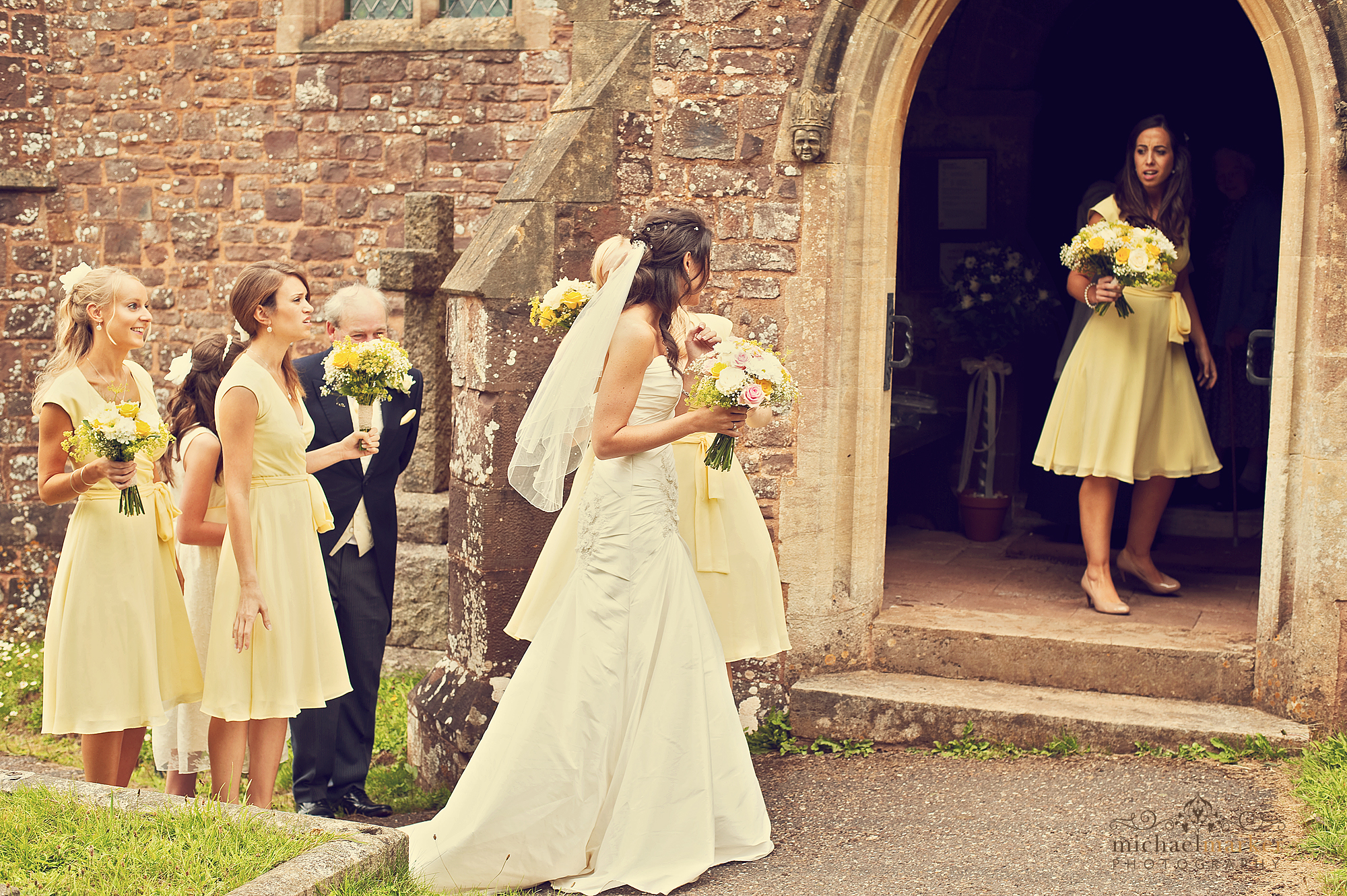 Bride-waiting-to-enter-Devon-village-church