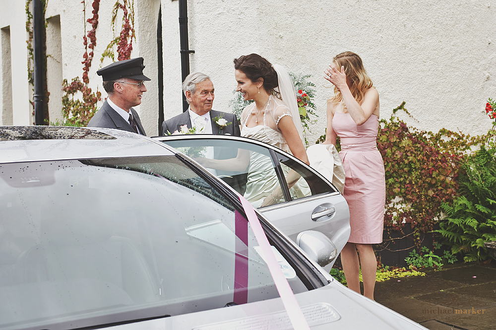 Bride getting into wedding car in Devon