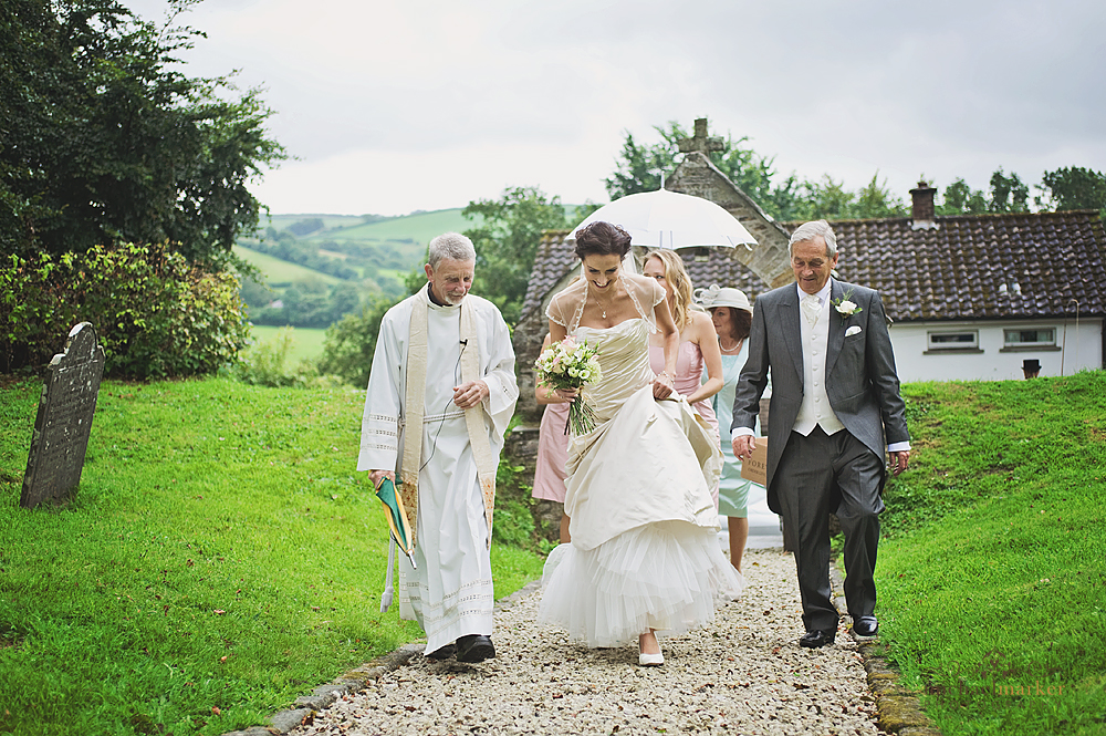 Bride and father walking up church path with vicar
