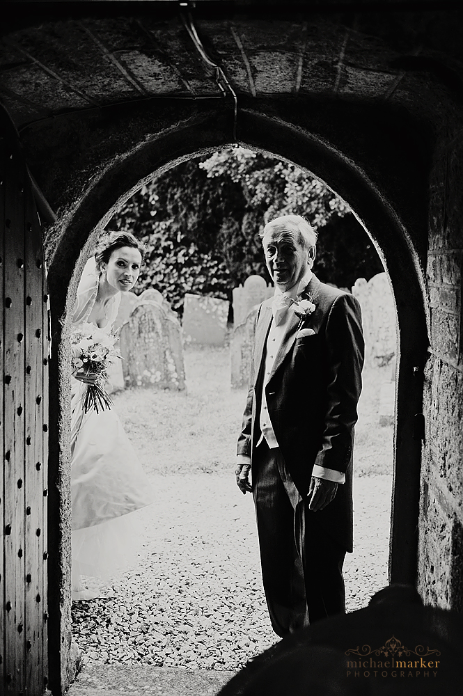 Bride and father looking through church doorway