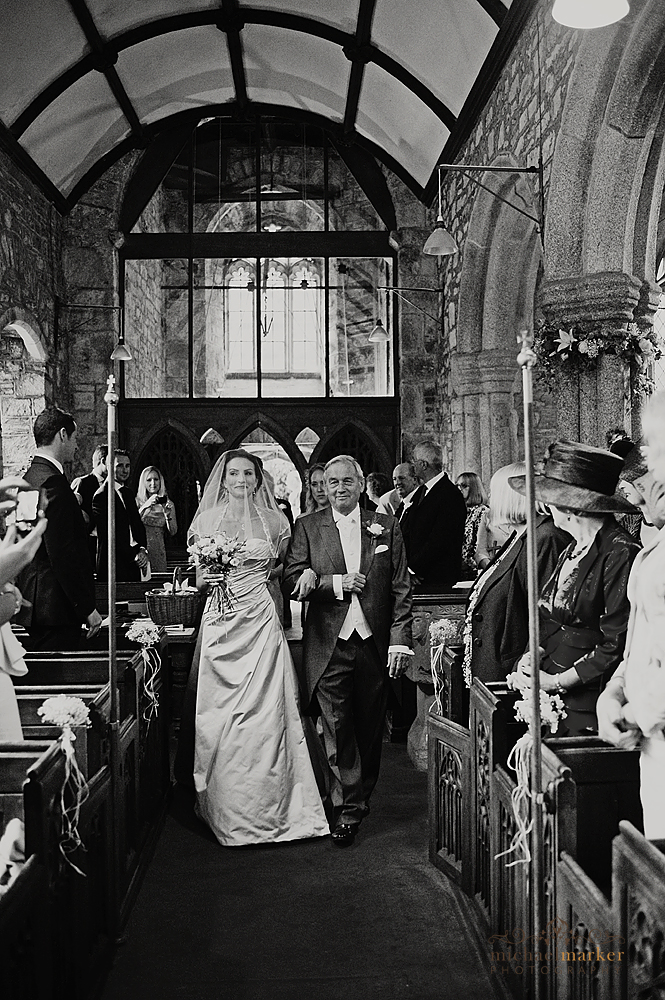 Bride and father walking down church aisle in devon