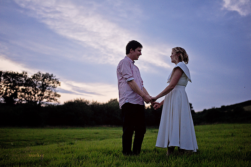 bride and groom in devon field at sunset