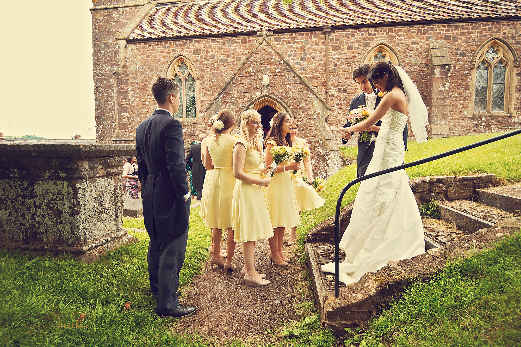 Bridal party waiting for guests in grounds of Bickleigh Church in Devon
