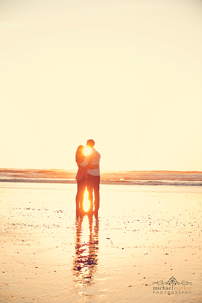 Couple silhouetted by setting sun at Polzeath for engagement shoot