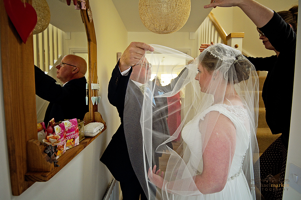 Father fixing brides veil before wedding in Launceston