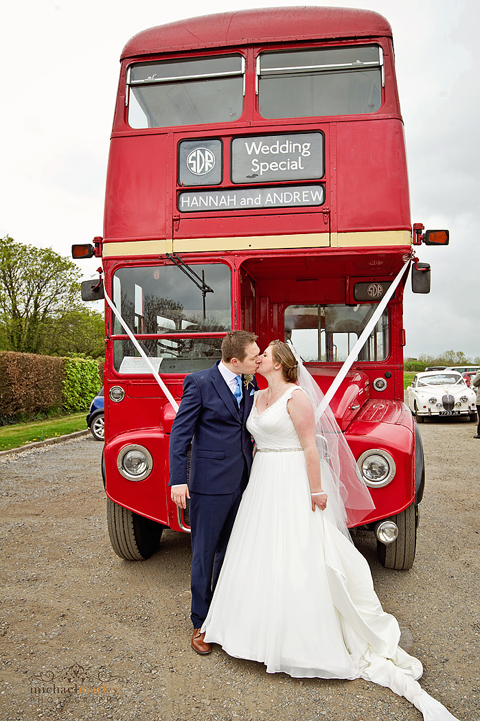 Bride and groom in front of vintage London routemaste bus at Lifton wedding in Devon