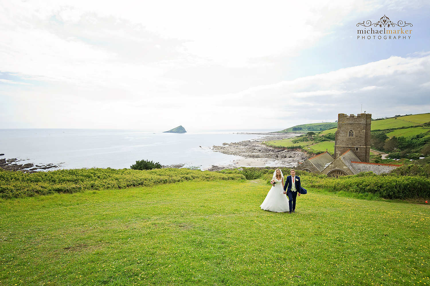 Bride and groom walking in fields behind Wembury Church with Plymouth and sea in the background