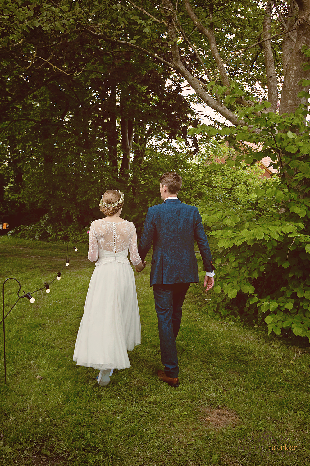 Bride and groom walk through orchard at Wiltshire wedding reception