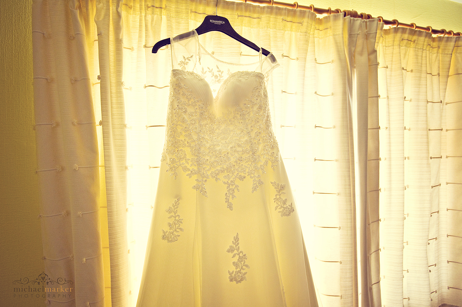 Beautiful embroidered wedding dress hanging in the window