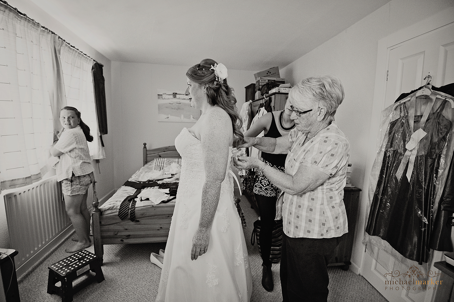 Bride getting dressed with her mother on her wedding day near Bath
