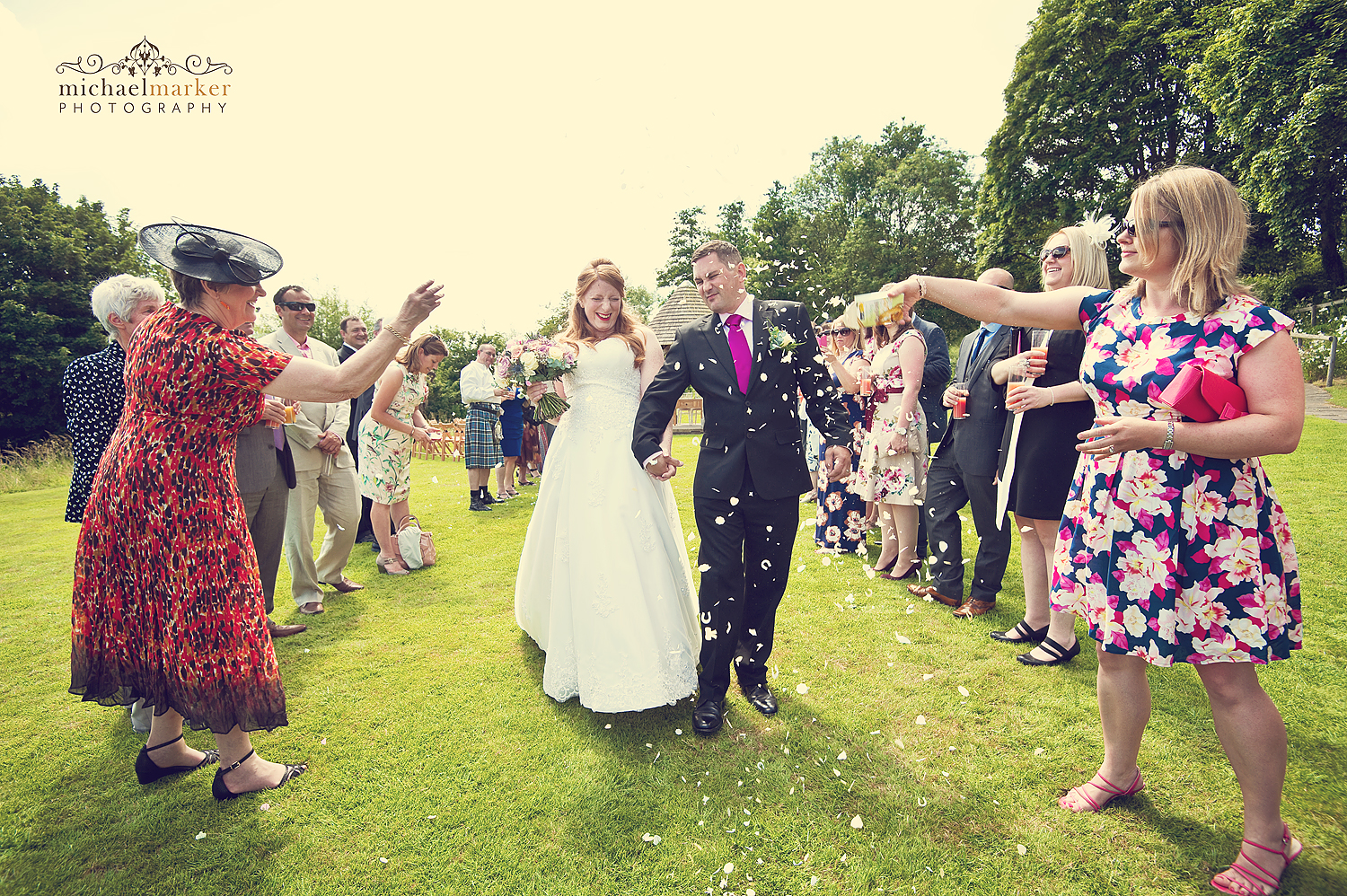 Guests throwing confetti at bride and groom at Priston Mill wedding