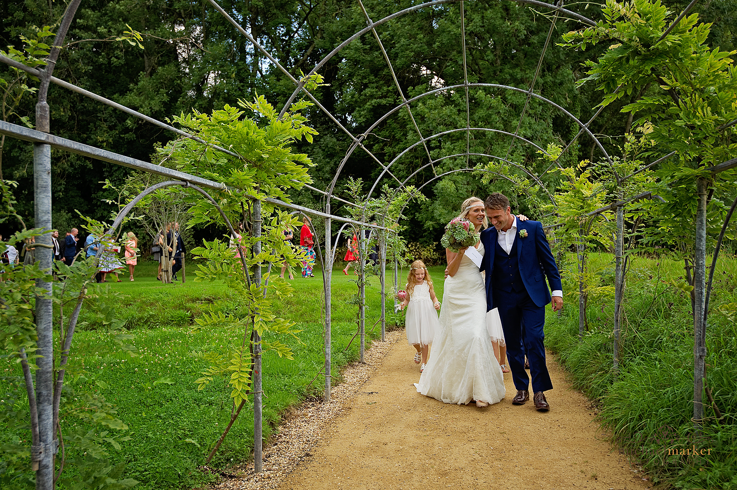 Bride and groom walking through the arbour walk at the Deer Park Hotel
