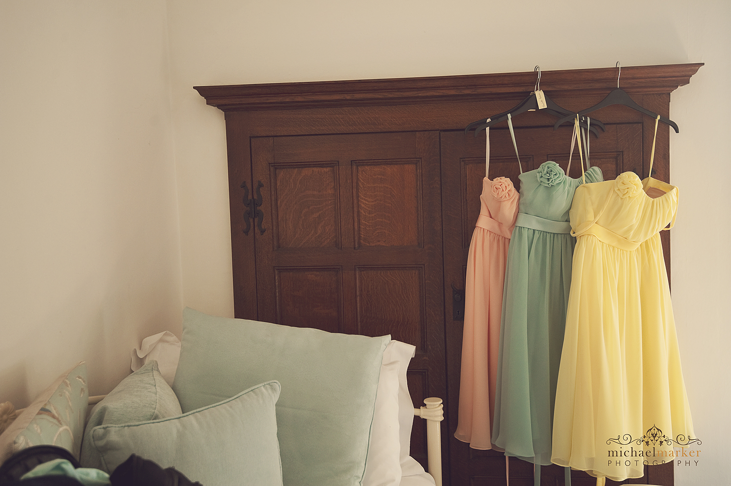 Pastel coloured bridesmaid dresses hanging up on wardrobe at Pickwell Manor in North Devon