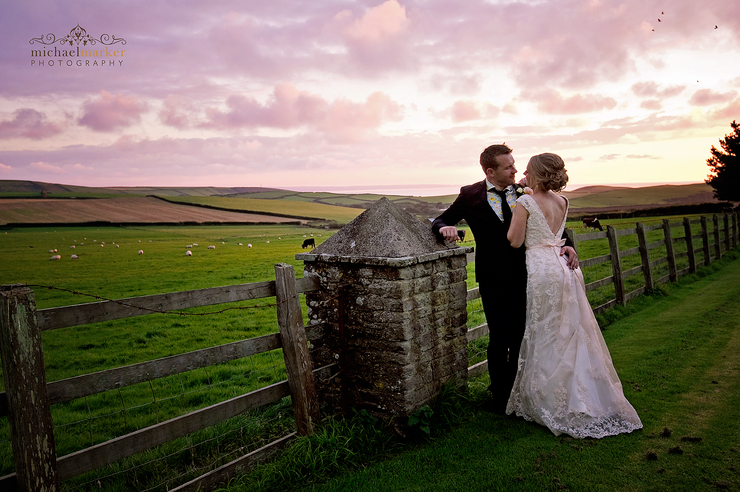 Bridal couple at sunset looking over devon fields to the sea