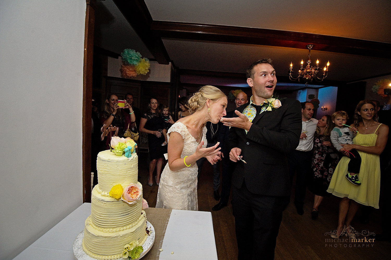 Documentary wedding photography moment of Bride licking cake off grooms fingers during cake cutting at wedding