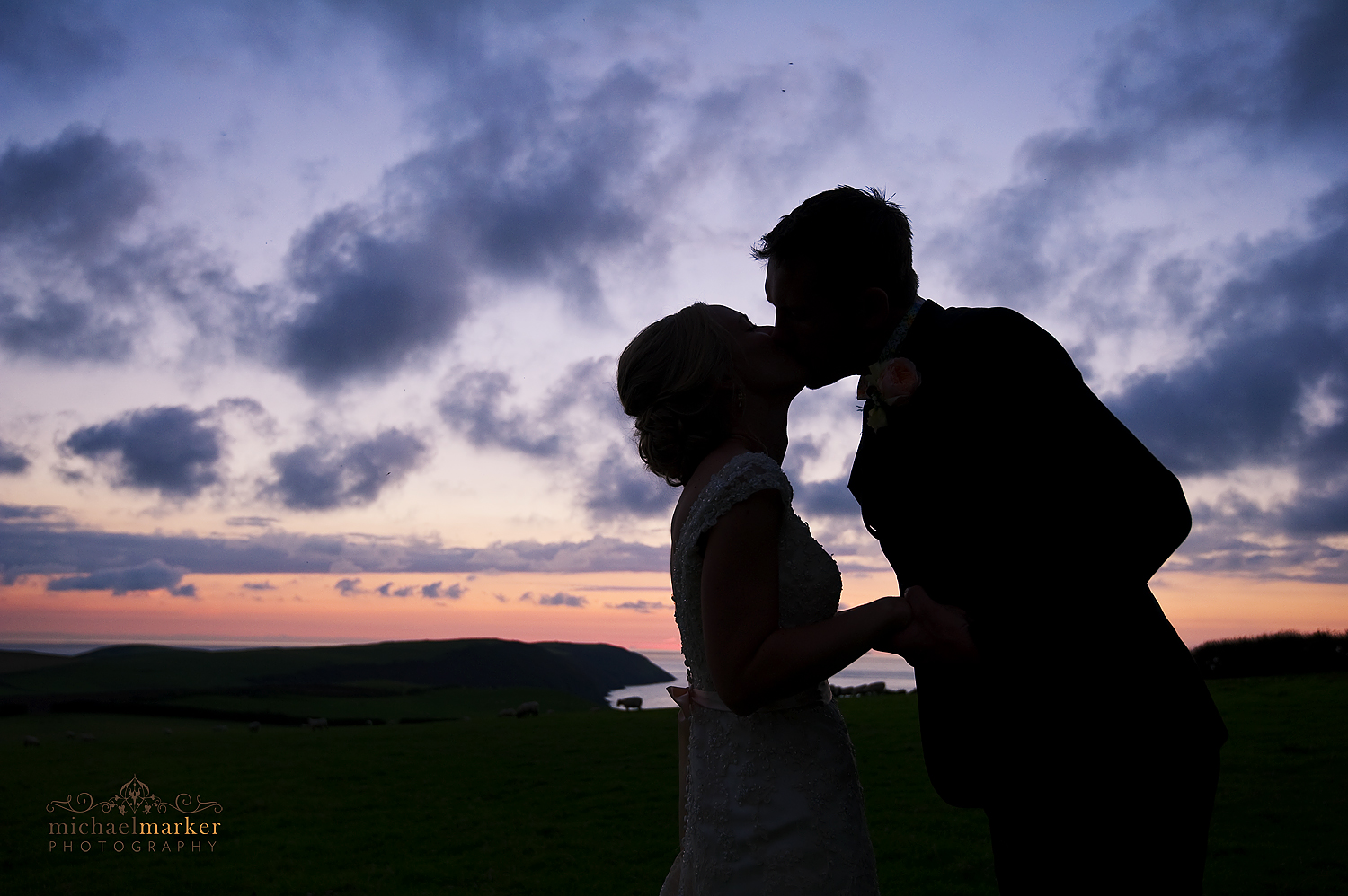 Sunset silhouette of bride and groom kissing at North devon wedding