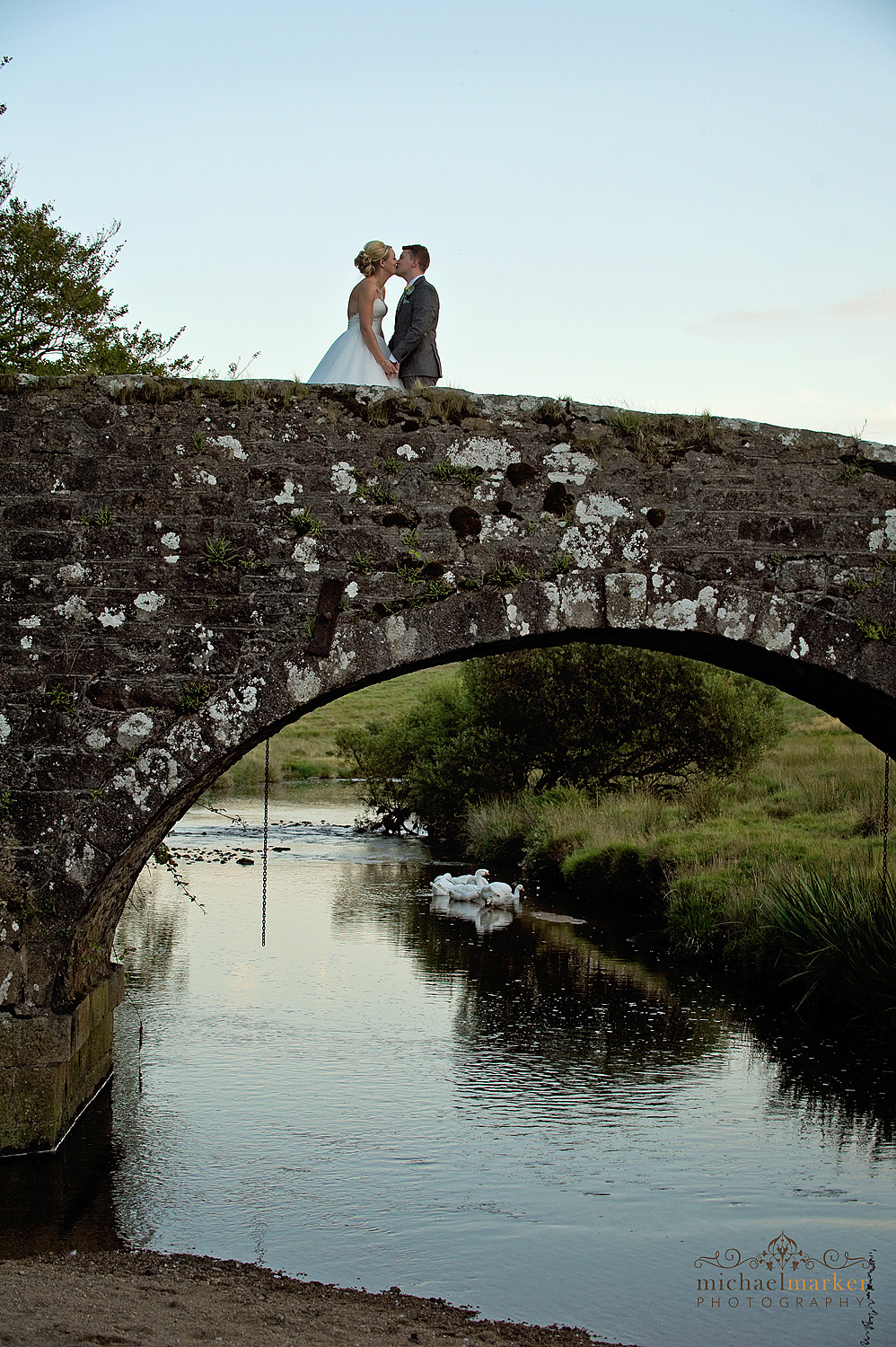 Bride and groom kissing on the bridge at sunset