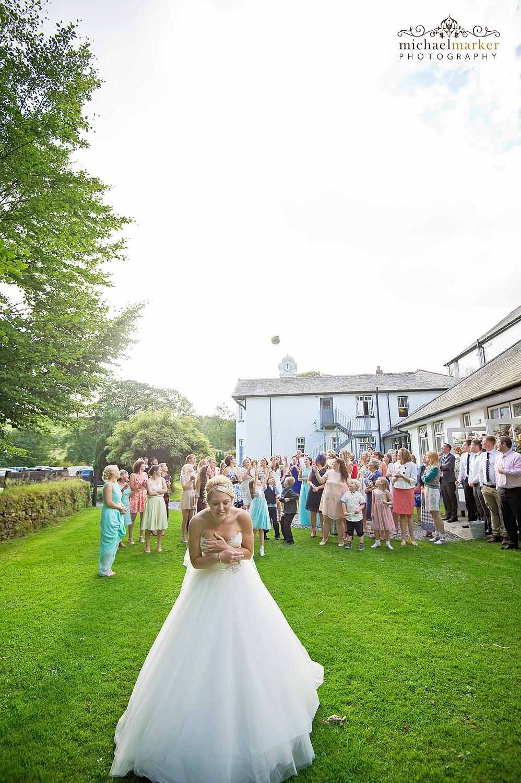 Bride throwing her bouquet in the gardens of the Two Bridges Hotel in Devon
