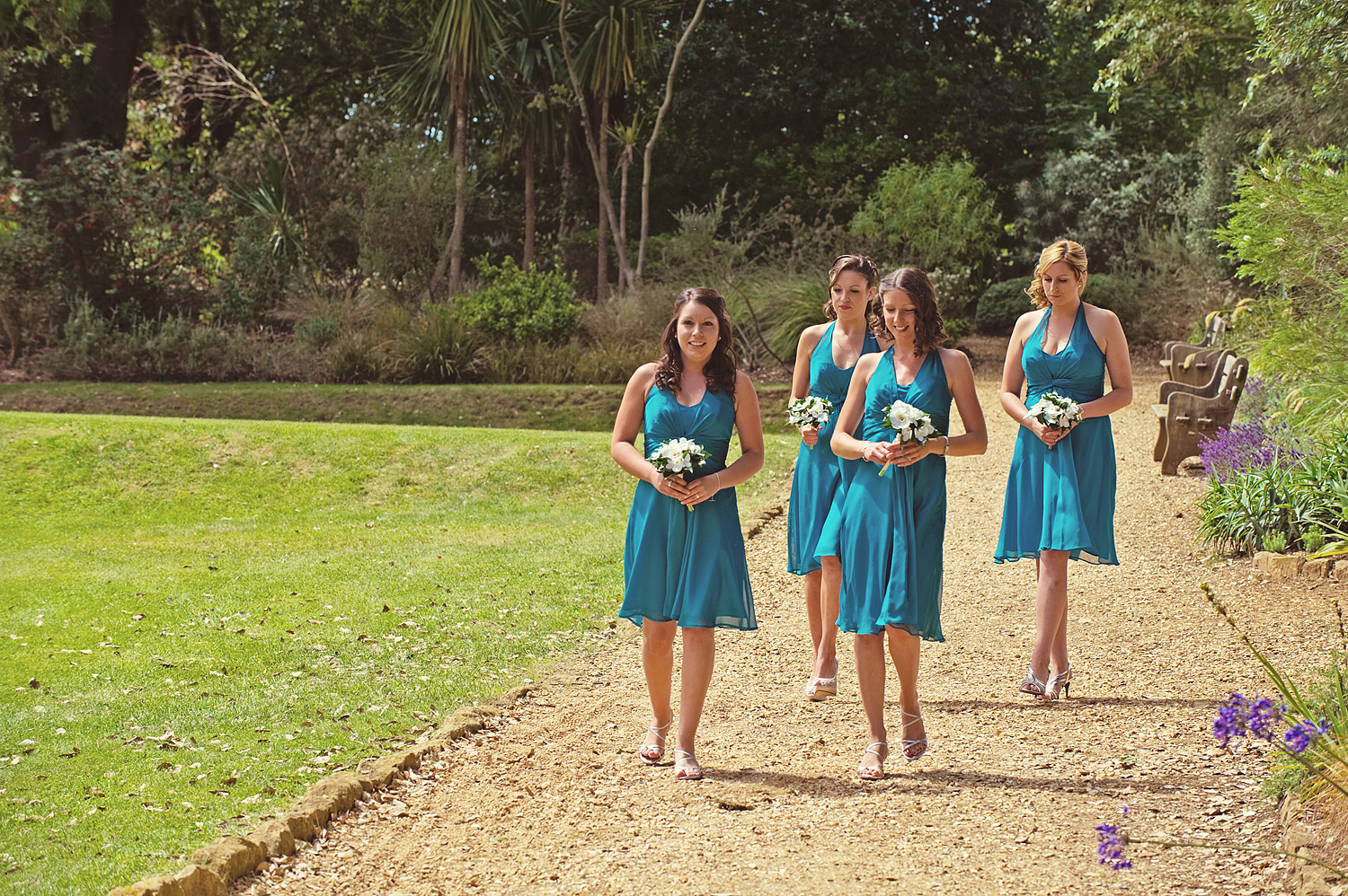 Four bridesmaids wearing blue dresses and holding bouquets walking towards pavilion at Abbotsbury Gardens wedding