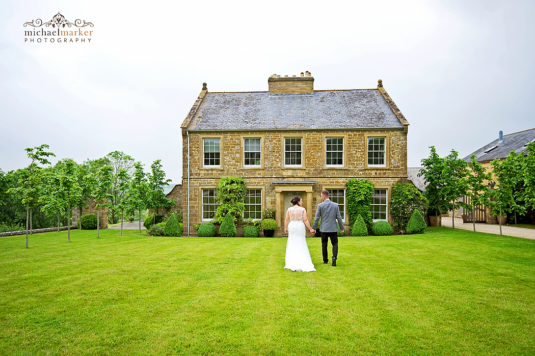 Bride and groom hand in hand in front of Axnoller House in Dorset