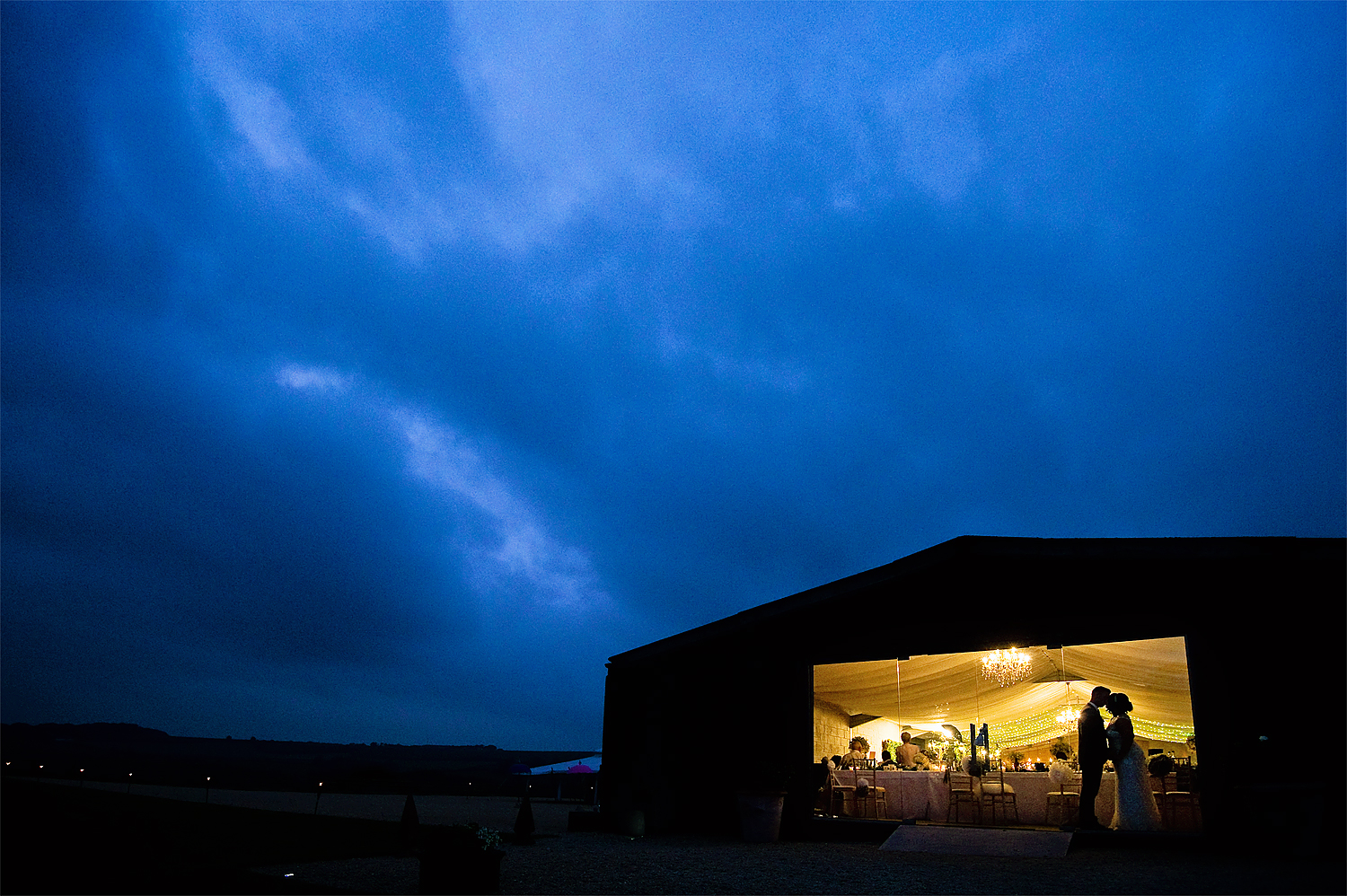 Silhouette of bride and groom in barn at Axnoller Farm weding in Dorset