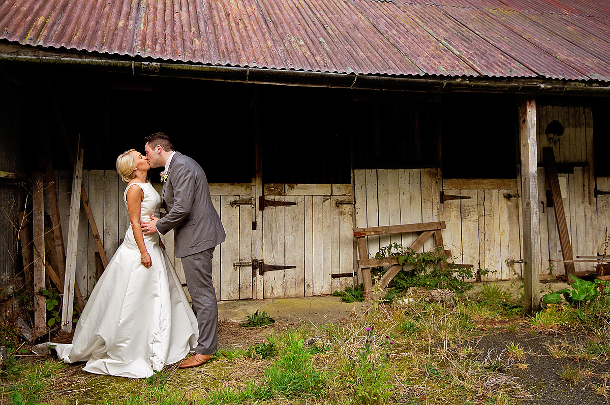 Bride and groom kissing in front of farm barns at Whitelady House on Dartmoor
