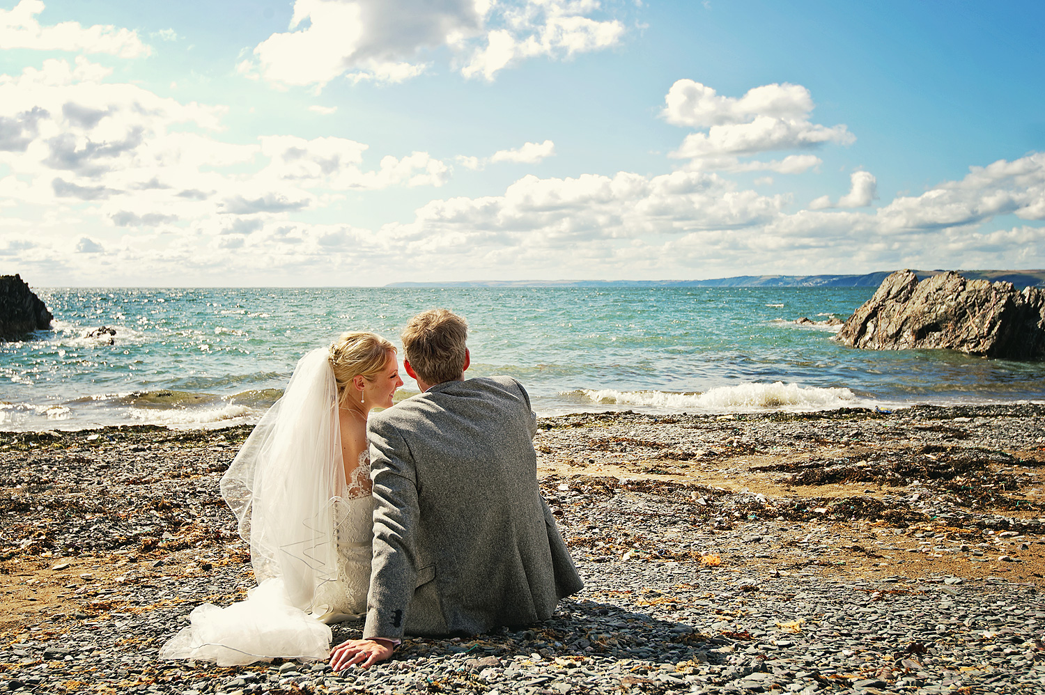 Bride and groom sat on beach at Polhawn fort wedding in Cornwall