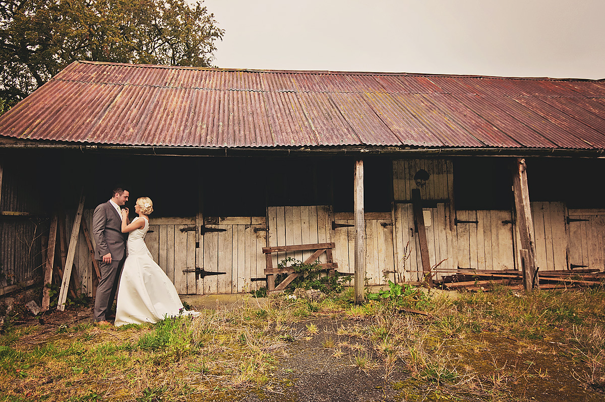 Bride and groom in front of stables at Bride and groom kissing in front of farm barns at Whitelady House on Dartmoor