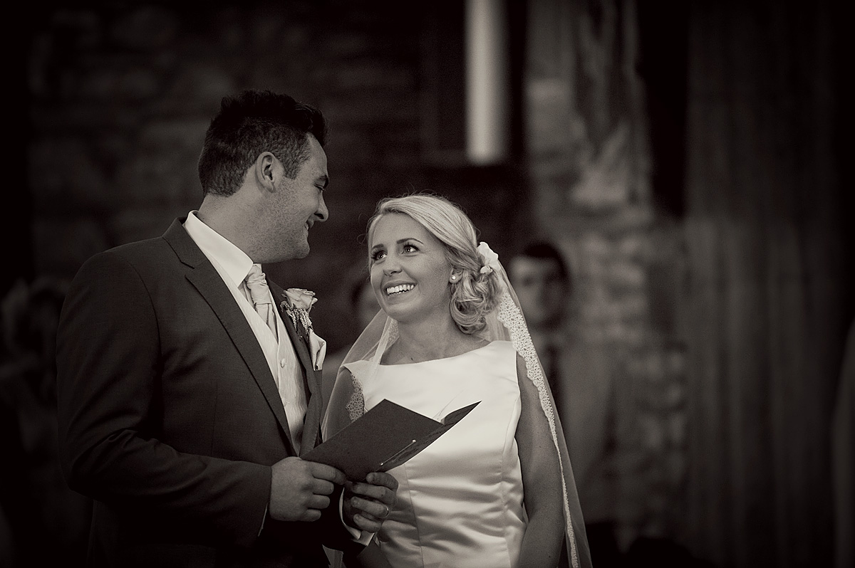 Bride and groom looking into each others eyes during wedding ceremony at Buckland Monochorum Church