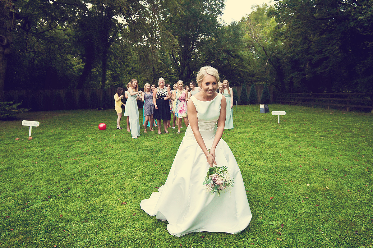 Bride about to throw wedding bouquet at Dartmoor wedding at Lydford