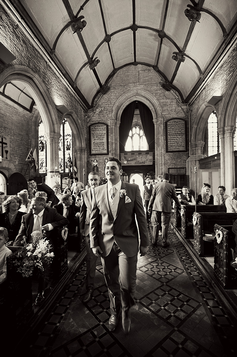 Groom and bestman walk down aisle of Buckland Monochurum church