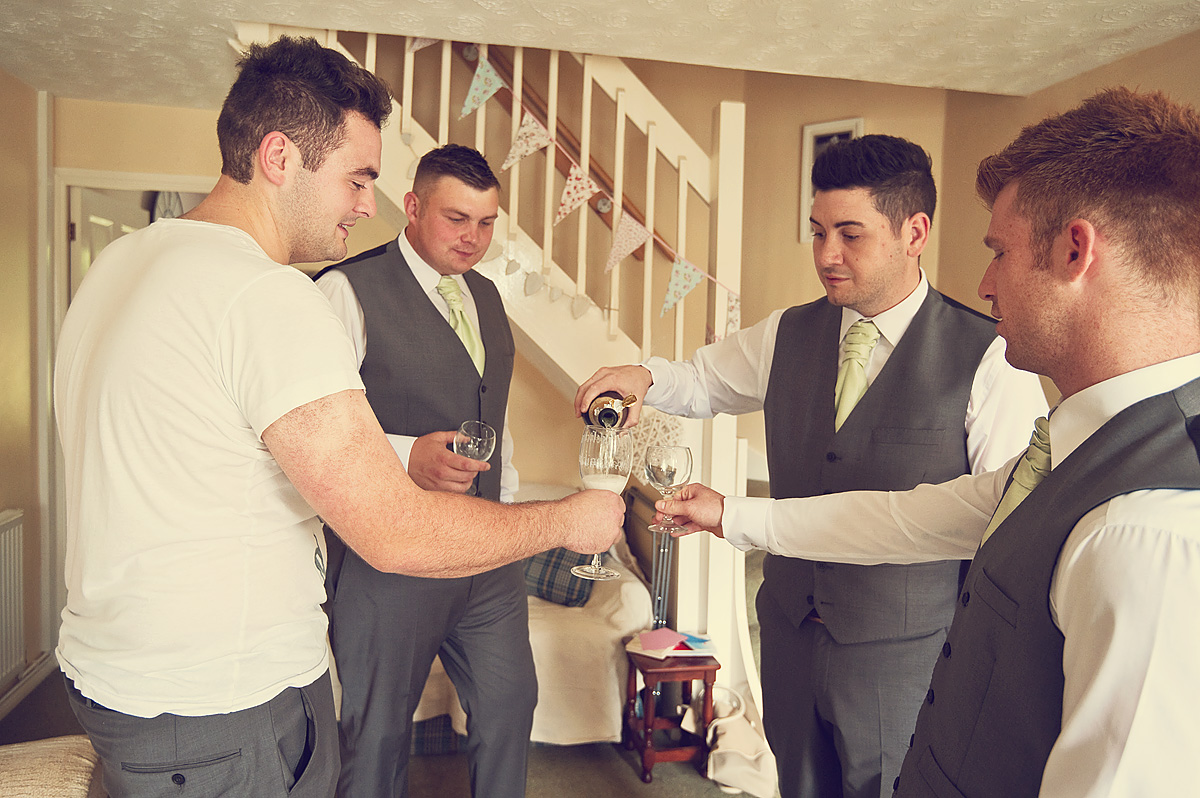 Groom and his ushers pour a glass of champagne on the morning of his wedding in Devon