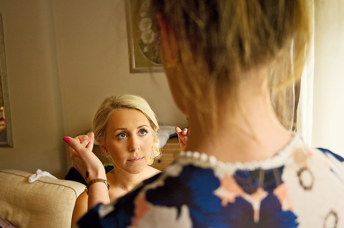 Bride looks at make up artist as she has her bridal make up applied