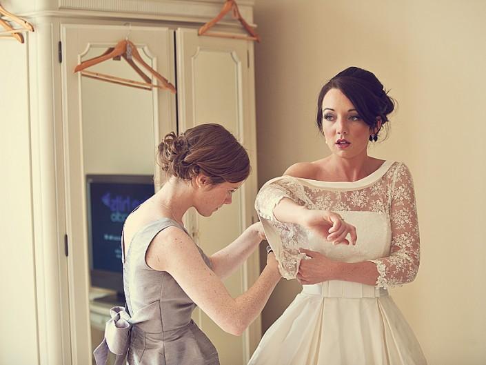 Bride putting her wedding dress on in the honeymoon suite at Langdon Court Hotel near Plymouth in Devon.