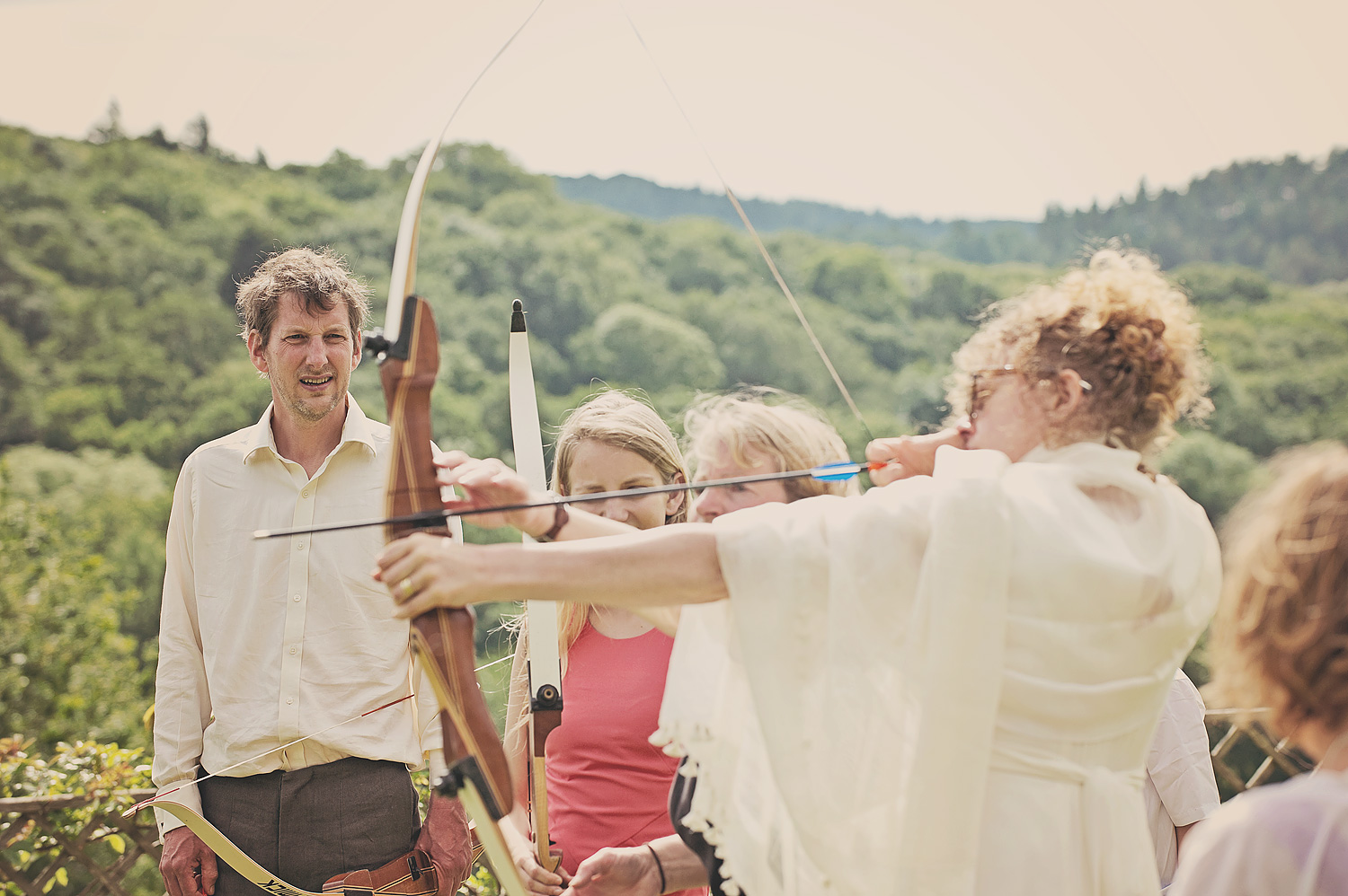 Bride taking part in archery at wedding celebrations at Hotel Endsleigh in Devon