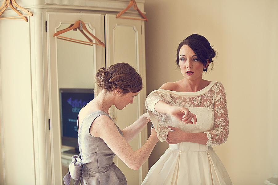 Bride putting her wedding dress on in the honeymoon suite at Langdon Court Hotel near Plymouth in Devon.