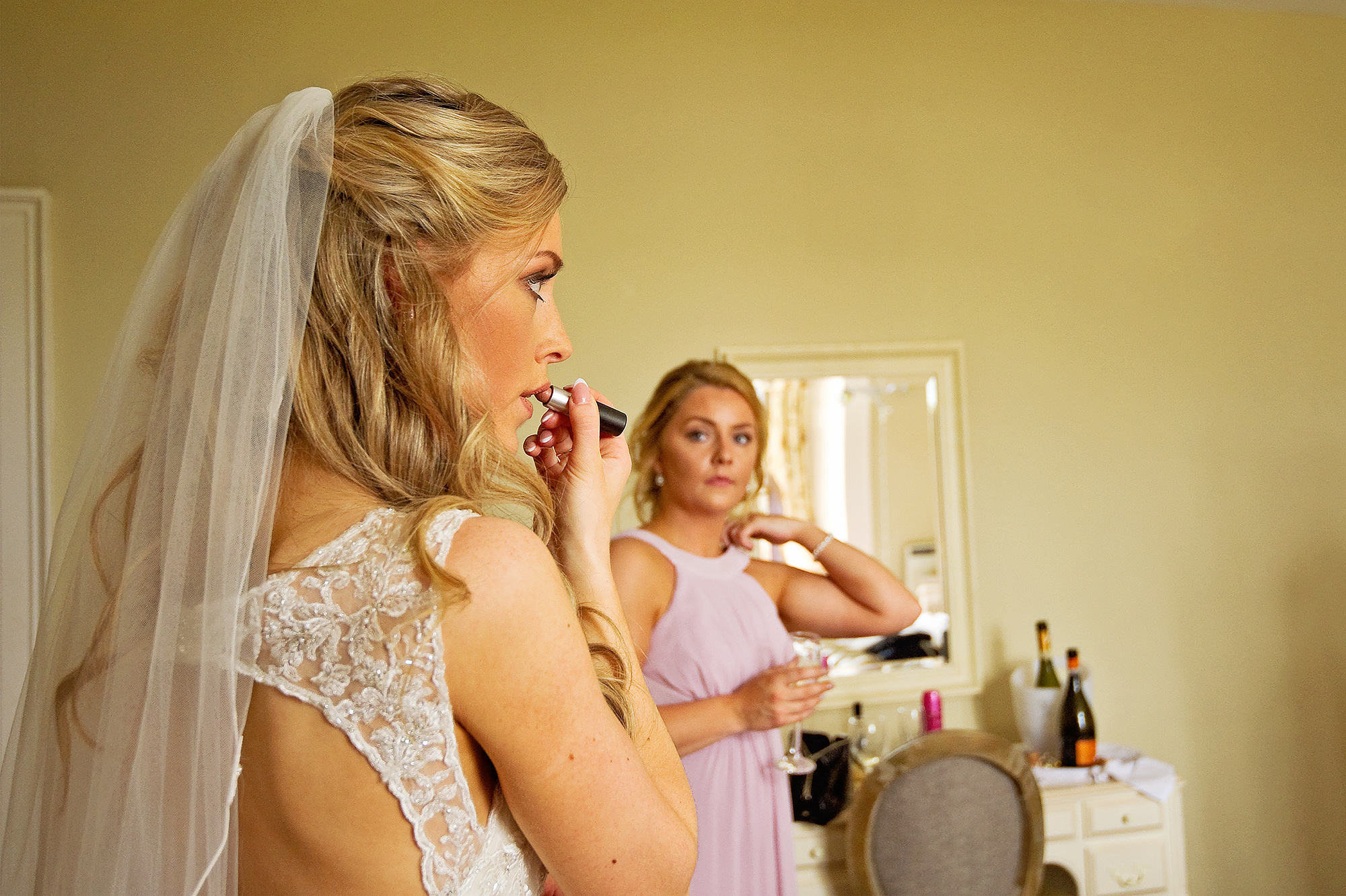Bride applying lipstick whilst bridesmaid looks on
