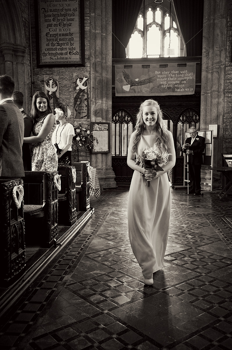 Bridesmaid walks down the aisle at Buckland Monochorum church in black and white