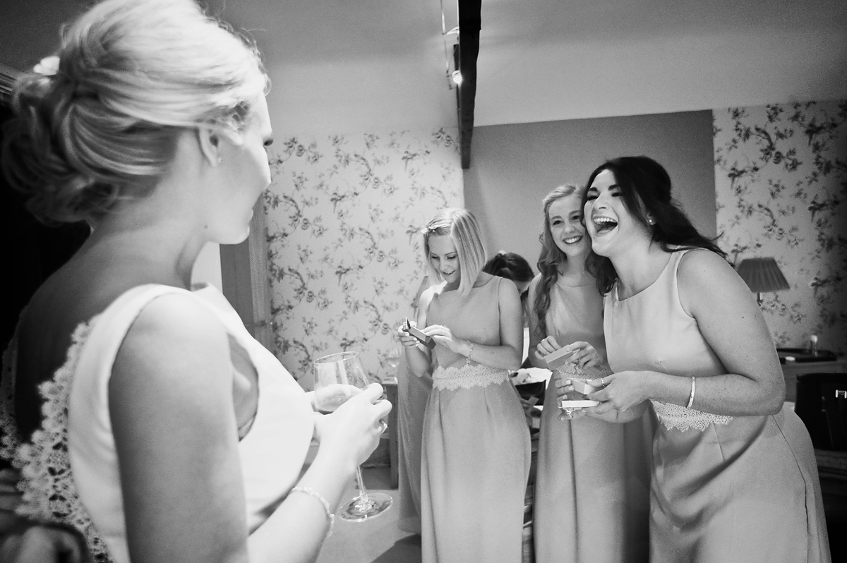 Bride giving gifts to her four bridesmaids in black and white