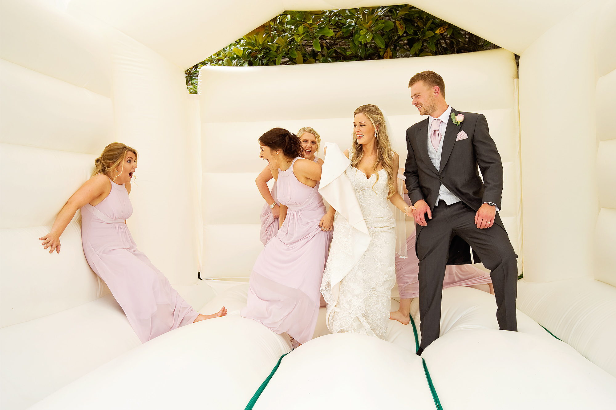 Bride and groom and bridesmaids having fun on a bouncy castle at Langdon Court