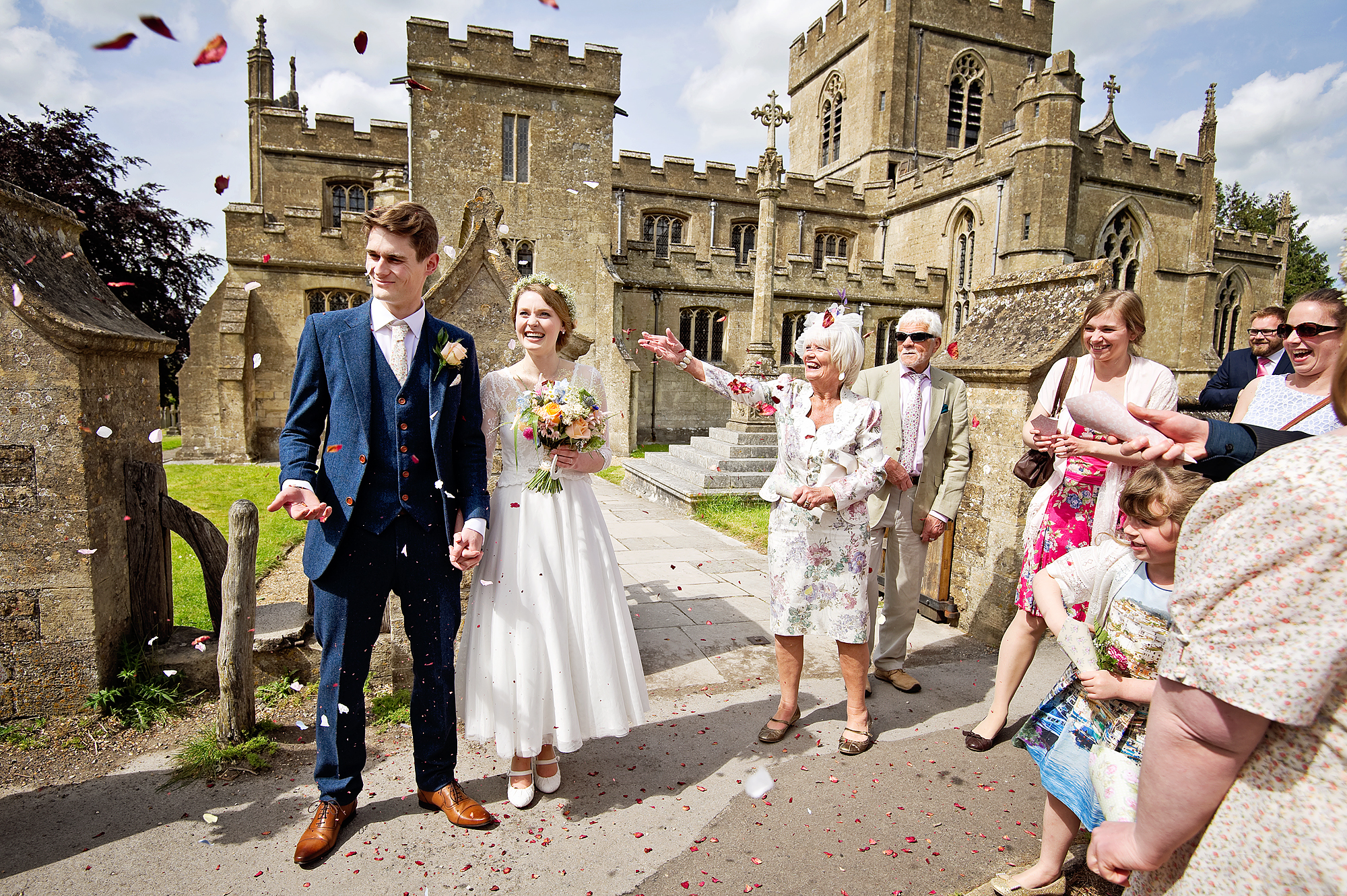 Guests throw confetti outside village church wedding in Wiltshire