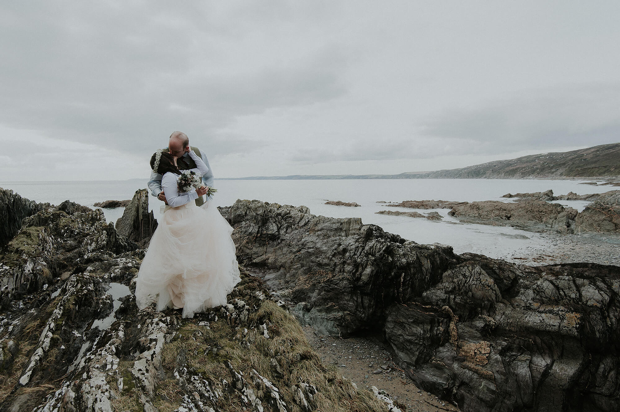 Bride and groom kiss on the beach at Polhawn Fort in Cornwall