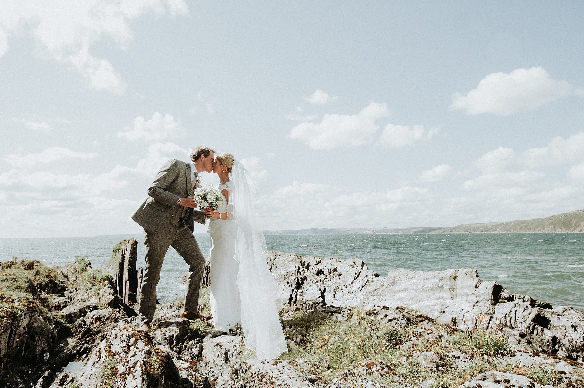 Beautiful bride and groom kiss on beach in Devon