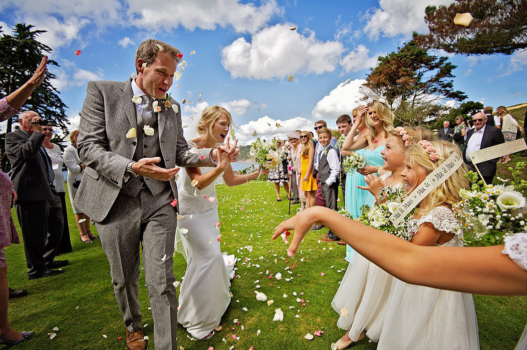 Beautiful young couple encouraging flowergirls to throw confetti at wedding at Polhawn Fort in Cornwall