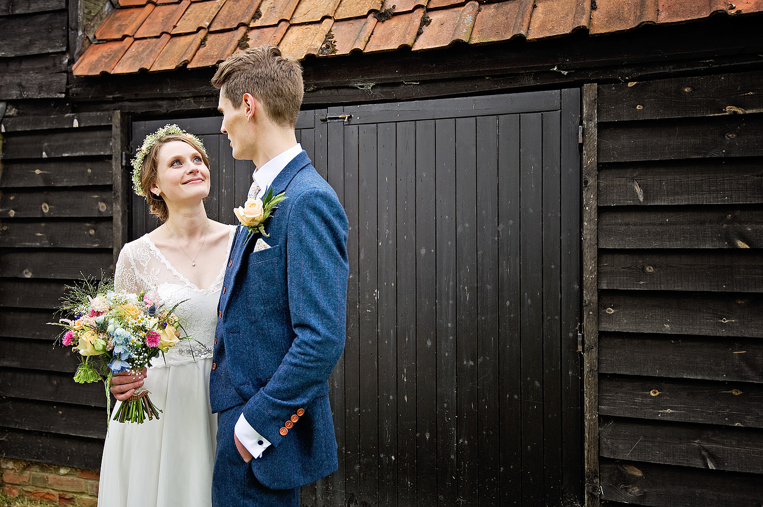 Bride looks into groom's eyes in front of a rustic barn at country styled wedding in the Home Counties.