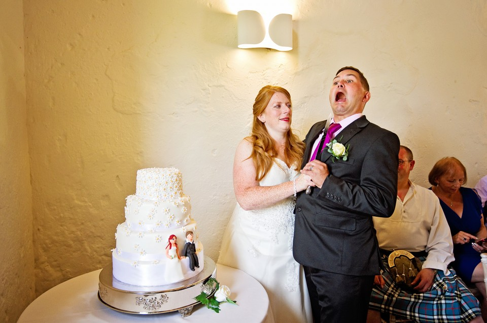 Funny cutting the cake photo at a Bath wedding as bride holds knife to groom's chin.