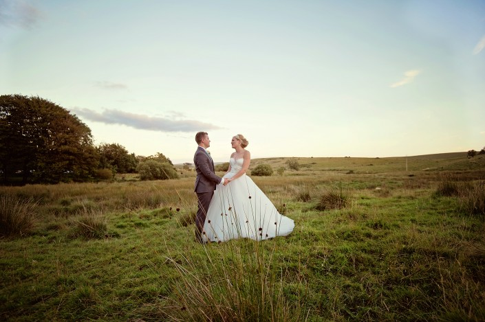 Bride and groom holding hands in field on Dartmoor near Two Bridges Hotel, Princetown